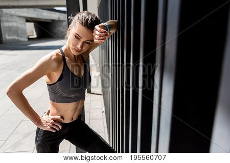 Beauty demands efforts. Portrait of exhausted young woman having rest after hard training. She is leaning on wall and looking aside pensively