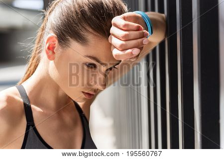 Portrait of sad young woman thinking about her career in sport. She is looking down with dissatisfaction while leaning elbow on fence. Tracker on her hand
