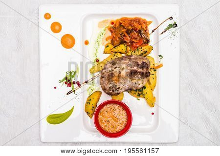 Top view bovine meat with potato and sauce decorated in white plate. Restaurant meal.