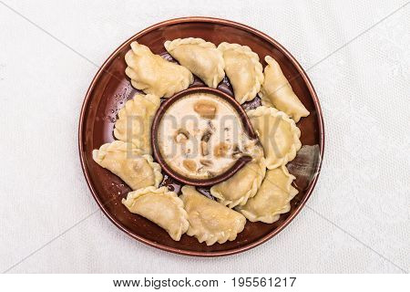 Fresh boiled ukrainian dumplings with cottage cheese or curd and butter in clay bowl. Varenyky or dumplings or pierogi is a traditional ukrainian meal. Restaurant meal.