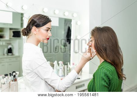 Attractive brunette girl primp at the mirror with lamps in the beauty studio. A happy satisfied customer of make-up and hairstyle service.