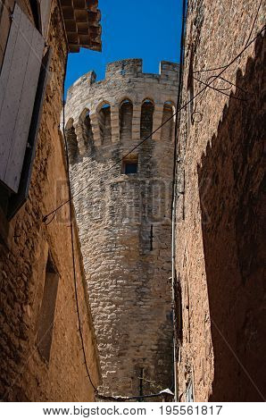 View of stone walls and castle tower in a narrow alley in the historical city center of Gordes. Located in the Vaucluse department, Provence region, in southeastern France