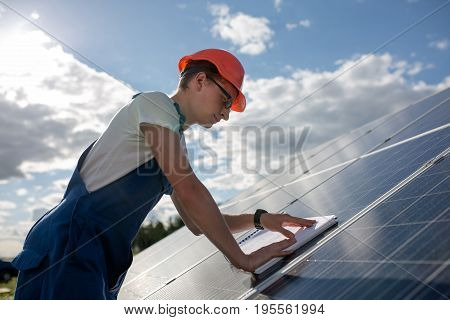 Side view on worker and solar panel. Employee working at solar energy station, blue sky and white clouds on backstage.