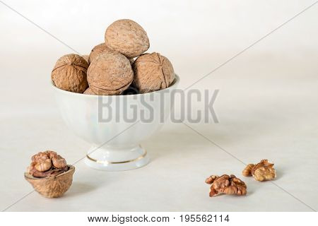 Walnut in a shell are stacked in a white cup. Next peeled nuts. Vegetable protein is an analogue of an animal. Light background