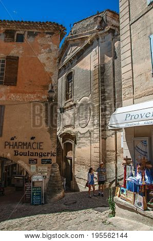 Gordes, France - July 03, 2016. View of alleyways with shops and church in the historical and lovely city center of Gordes. Located in the Vaucluse department, Provence region, southeastern France