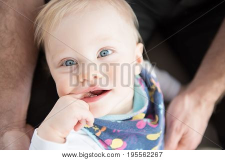 Close Up Of Beautiful And Happy Baby Girl With Blue Eyes. Top View.