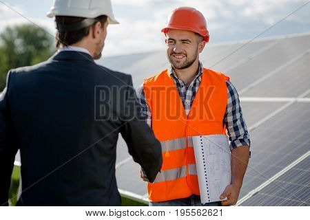 Foreman and businessman concluding a treaty. Agreement between two sides at solar energy station.