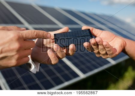 Solar energy, two hands holding photovoltaic item. Solar panels in the field, close yp view on photovoltanic detail.