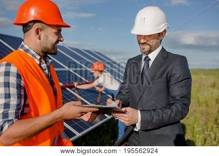 Client signing agreement at solar energy station. Director and foreman signing papers while worker checking out solar panel behind them.