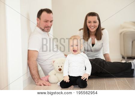Happy Family Of Three  Is Enjoying At Home. Parents And Their Beautiful Baby Girl Sitting On The Gro