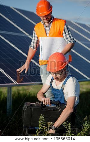 Workers at solar power station. Technicians checking out solar power panels.