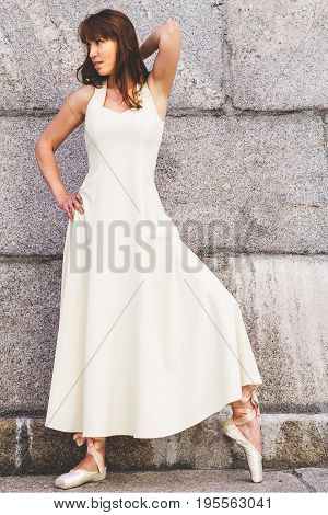 Portrait of the beautiful modern ballerina danсing in long white dress outdoors