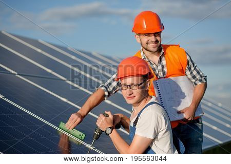 Engineers installing solar panels. Workers with tools maintaining photovoltaic panels.