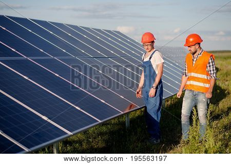 View on photovoltaic panels of solar power station. Foreman and technician looking at solar energy panel.