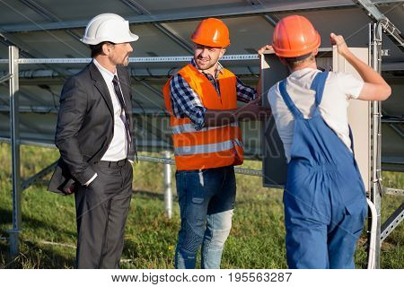 Engineers offering business client to look at electrical box. Businessman examining electrical box with technicians.