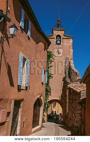Roussillon, France - July 03, 2016. View of traditional colorful houses in ocher and clock tower, in the historic Roussillon. Located in the Vaucluse department, Provence region, southeastern France