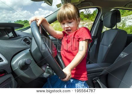 Little pretty girl having hard time driving a car