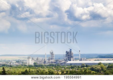 Industrial cement factory with pipes smoking and puffy clouds above