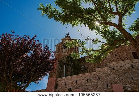View of old church made of stone against the sunlight, in the city center of the village of Roussillon, under a sunny blue sky. Located in the Vaucluse department, Provence region, southeastern France