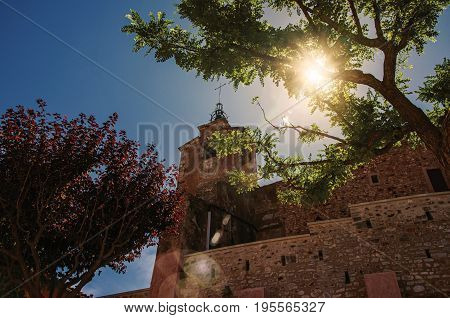 View of old church against the sunlight, in the city center of the Roussillon village, under a sunny blue sky. Located in the Vaucluse department, Provence region, southeastern France. Retouched photo