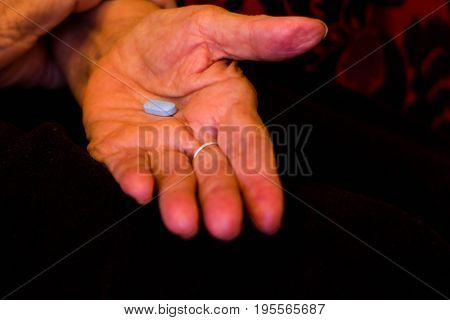 Hand of an older woman holding colored medicines