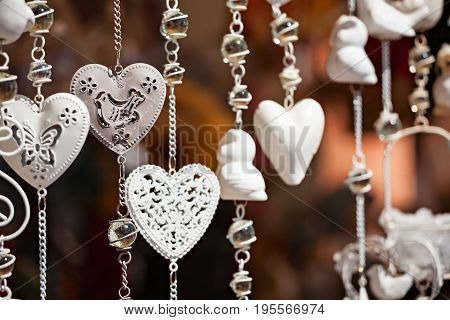 White hanging heart souvenirs in a market