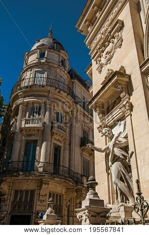 Close-up of buildings in the city center of Nimes, with statues, decorative details on the walls and blue sky. Located in the Gard department, Occitanie region in southern France