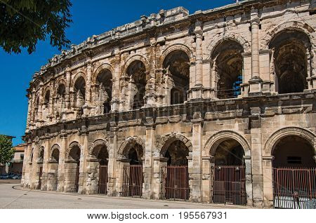 Partial view of the exterior of the Arena of Nimes, an amphitheater of the Roman Era, with sunny blue sky. Located in the Gard department, Occitanie region in southern France