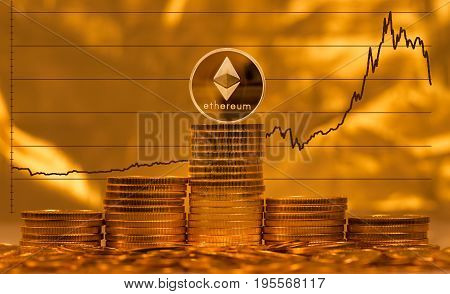 Single ethereum coin on stack of gold coins with graph of price change against US dollar in background