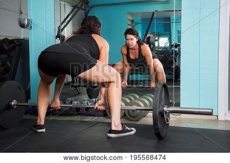 A muscular female weight trainer prepares to do a deadlift while looking intensely into the mirror.