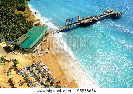 Aerial View of Beautiful Summer Beach with People, Warm Blue Sea, Pier and Umbrellas. Travel and Vacation Concept.