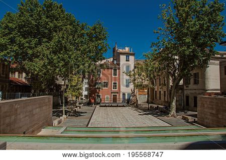 Quiet square with pond, trees, buildings and blue sky in the city center of Nimes. Located in the Gard department, Occitanie region in southern France