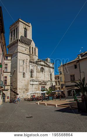 Nimes, France - July 04, 2016. Square with restaurants, buildings, church and blue sky in city center of the ancient town of Nimes. Located in the Gard department, Occitanie region, southern France