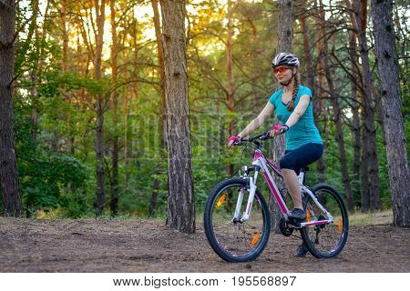 Young Woman Riding the Bike on the Trail in the Beautiful Fairy Pine Forest. Adventure and Travel Concept.