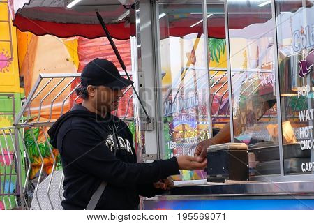 Coquitlam, BC, Canada - April 09, 2017 : People buying donuts and paying cash at the West Coast Amusements Carnival
