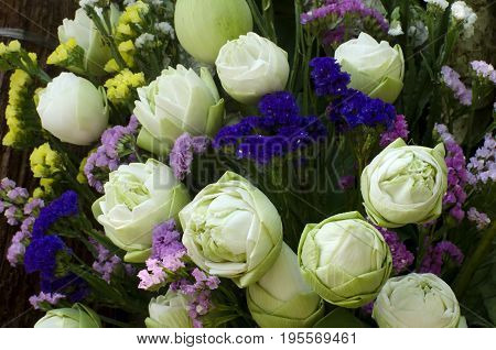 A white lotus that fold a petal with purple blue and yellow statice flower design and decorate in a bouquet