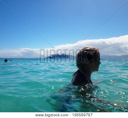Swimmer In The Water With Cruise Ship, Doini Island, Papua New Guinea.