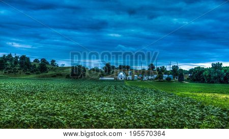 Farmhouse with corn fields tress and clouds