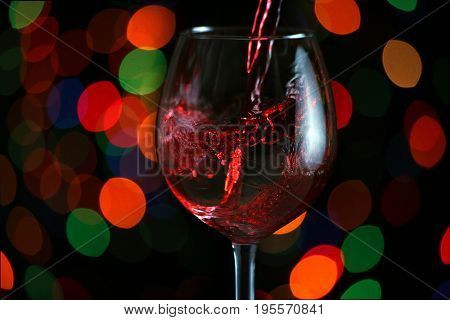 Beautiful splash of red wine in a glass against the festive lights