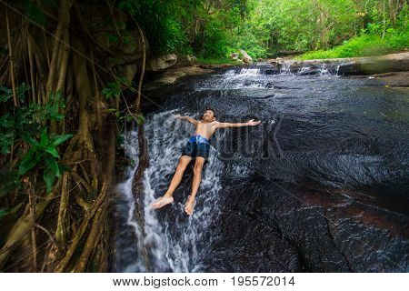 Boy are soaking the stream from the stream that flows down the mountain happily with nature Dark tones