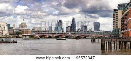 Panorama of a wharf on the River Thames, with Blackfriars Bridge, St Paul' Cathedral and the City of London beyond.