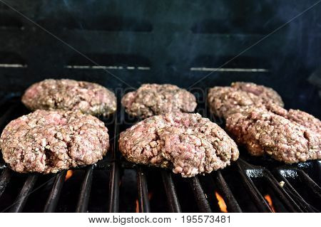 Six raw hamburgers cooking on a gas grill