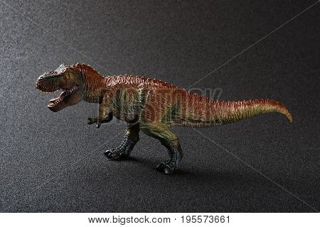 a tyrannosaurus toy on a dark background