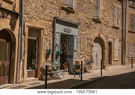 Lourmarin, France - July 07, 2016. View of typical stone houses and shops on a street of the historical village of Lourmarin. Located in the Vaucluse department, Provence region, southeastern France