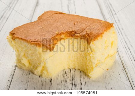 sponge cake on white wood background with a bite