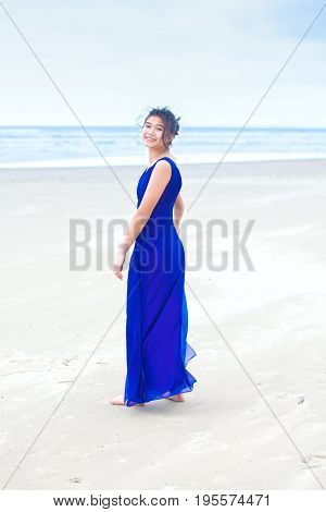 Beautiful biracial teen girl wearing bright blue dress standing on beach with ocean in the background looking back over shoulder
