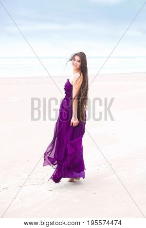 Beautiful biracial teen girl wearing purple dress standing on beach with ocean in the background looking back over shoulder