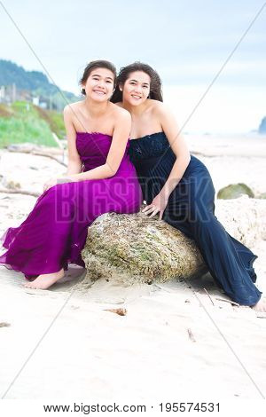 Two beautiful biracial Asian Caucasian teen girls in elegant dresses smiling together on the beach with ocean in the background