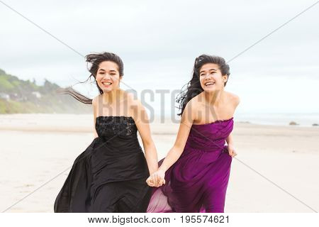 Two biracial Asian Caucasian teenage girls in formal dresses talking while running along beach on cool cloudy day
