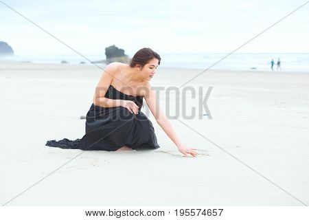 Beautiful biracial teen girl wearing formal dress kneeling down writing in sand on beach by ocean